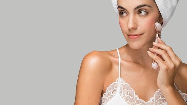 Vrouw haar gezicht kopie ruimte masseren