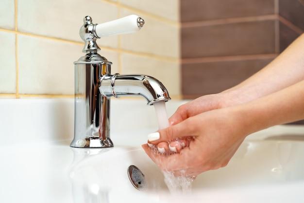 Vrouw haar handen wassen met zeep in de badkamer