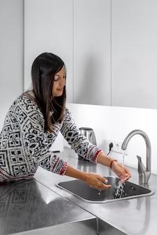 Vrouw haar handen wassen na het koken
