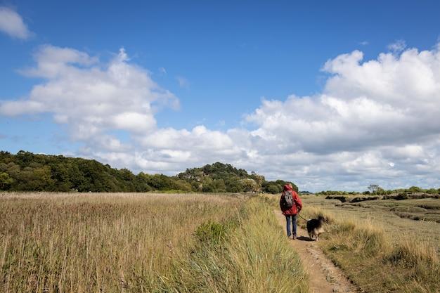 Vrouw haar hond wandelen op een veld