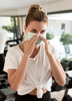 Vrouw haar medische masker in de sportschool aanpassen