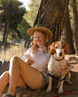 Vrouw haar schattige hond aaien en met behulp van haar mobiele telefoon