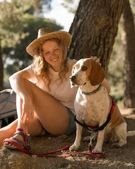 Vrouw haar schattige hond aaien en op de grond zitten