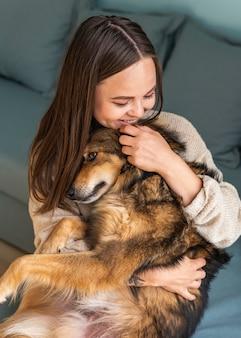 Vrouw haar schattige hond thuis aaien tijdens de pandemie