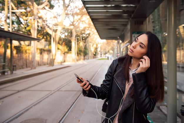 Vrouw haar telefoon oortelefoons zetten