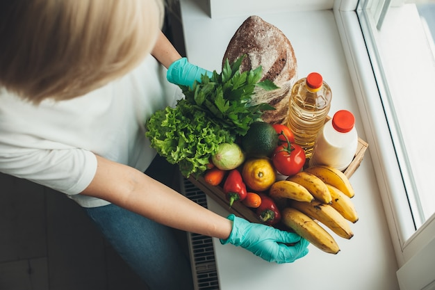 Vrouw hamsteren met fruit en groenten terwijl ze handschoenen draagt tijdens de quarantaine