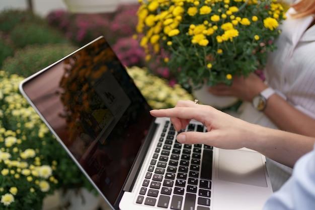 Vrouw hand bloemen opties presenteren aan een potentiële klant detailhandelaar met behulp van laptop. zakelijke discussie, planning van toekomstige samenwerking terwijl u de voorwaarden noteert en onderhandelt