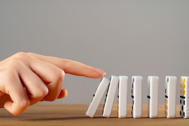 Vrouw hand domino omverwerpen. kettingreactie bedrijfsconcept