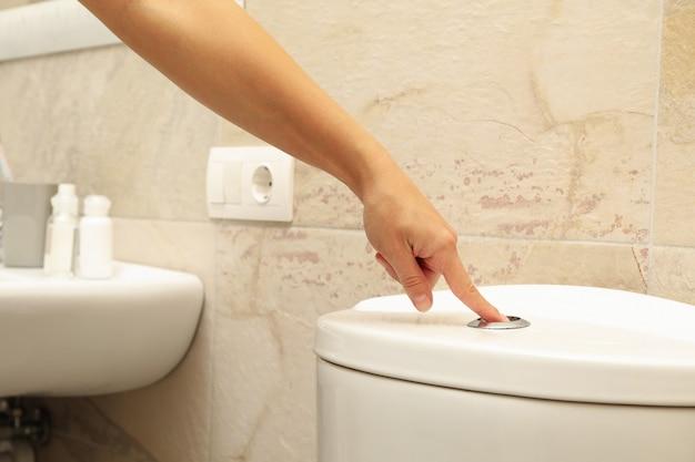 Vrouw hand drukt op de knop van de toiletspoeling