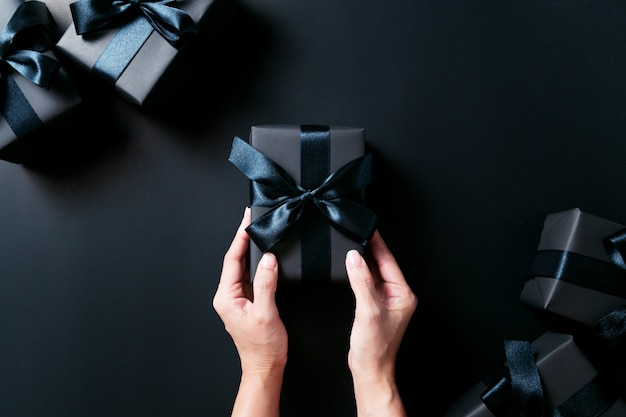 Vrouw hand geven de geschenkdoos op zwarte achtergrond Premium Foto