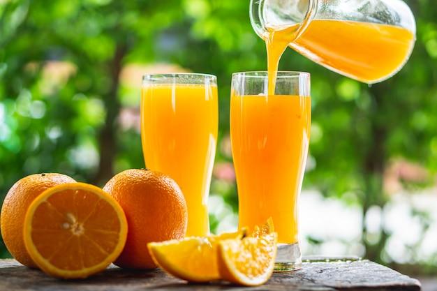 Vrouw hand gieten jus d'orange in glazen