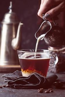 Vrouw hand gieten melk in glas kopje koffie