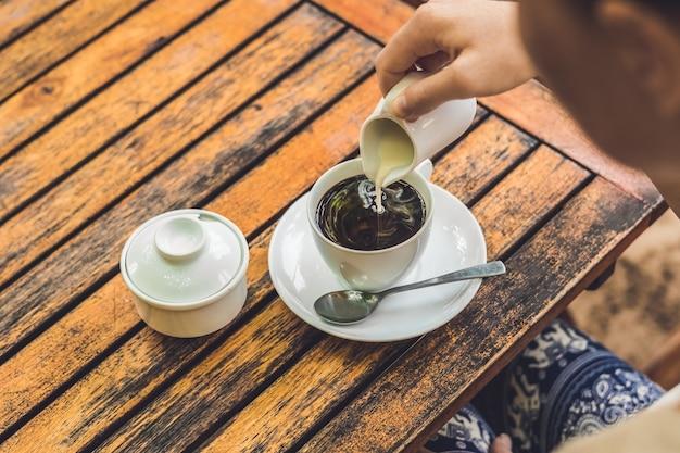 Vrouw hand gieten melk in witte kopje koffie op terras