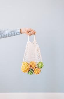 Vrouw hand houden eco mesh tas met vers fruit op blauwe achtergrond.