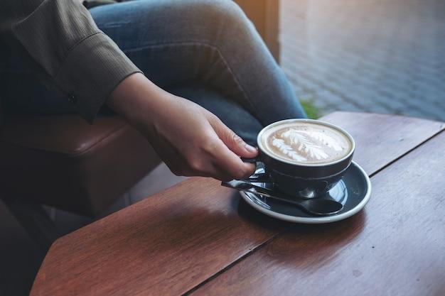 Vrouw hand houden en hete latte koffie drinken zittend in café