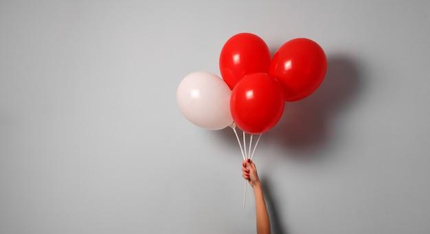 Vrouw hand houden rode en witte luchtballon