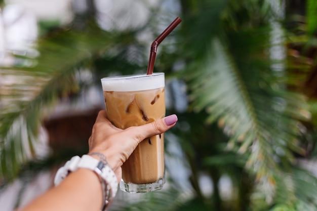 Vrouw hand houdt ijs latte over groene tropische struiken