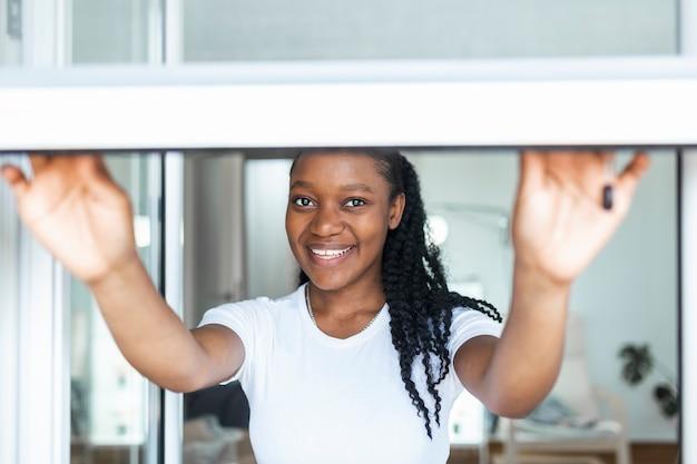 Vrouw hand houdt intrekbare geplooide horhouder om het raam te openen of te sluiten, muskietennetten