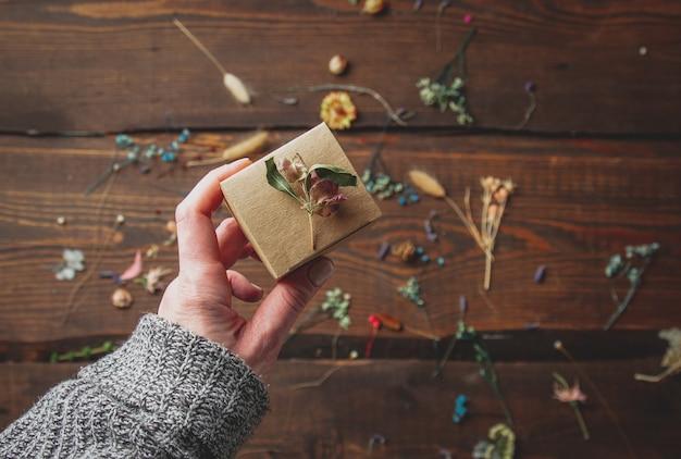 Vrouw hand houdt kleine handgemaakte geschenkdoos naast droge kruiden op houten tafel