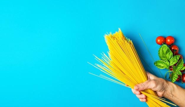 Vrouw hand houdt pasta in de buurt van tomaten en basilicum bladeren
