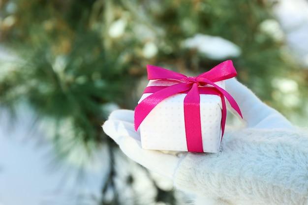 Vrouw hand in gebreide want met cadeau