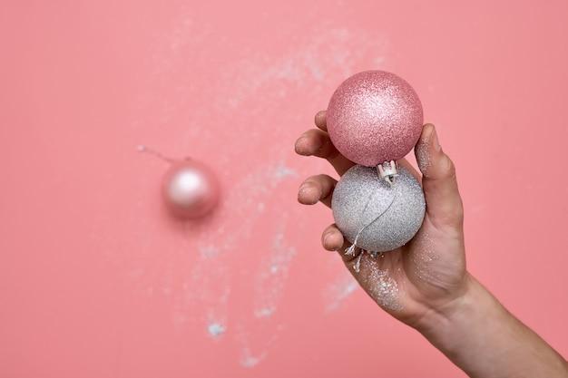 Vrouw hand in glitter. met de hand gemaakte kerstboomballen. diy ambacht.