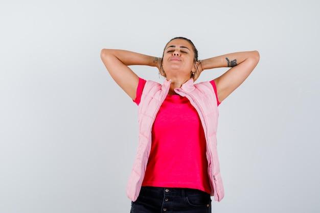 Vrouw hand in hand achter hoofd in t-shirt, vest en ziet er ontspannen uit