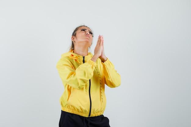 Vrouw hand in hand in gebed gebaar in sport pak en op zoek hoopvol. vooraanzicht.