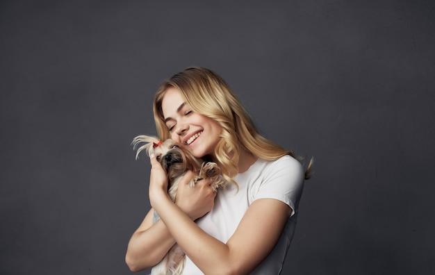 Vrouw hand in hand kleine rashond vriendschap knuffel vreugde grijze muur.
