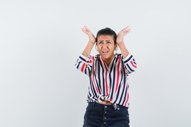 Vrouw hand in hand op hoofd in shirt, rok en op zoek geïrriteerd