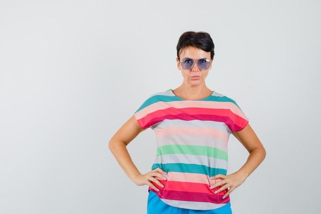 Vrouw hand in hand op taille in gestreept t-shirt, broek en op zoek zelfverzekerd