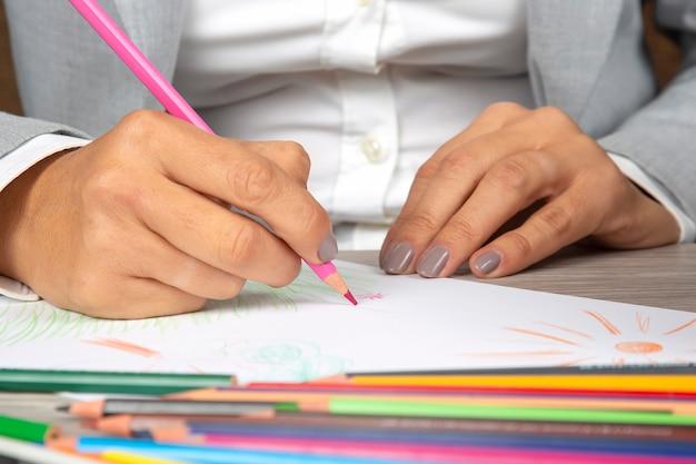 Vrouw hand in het kantoor tekent met kleurpotloden op papier