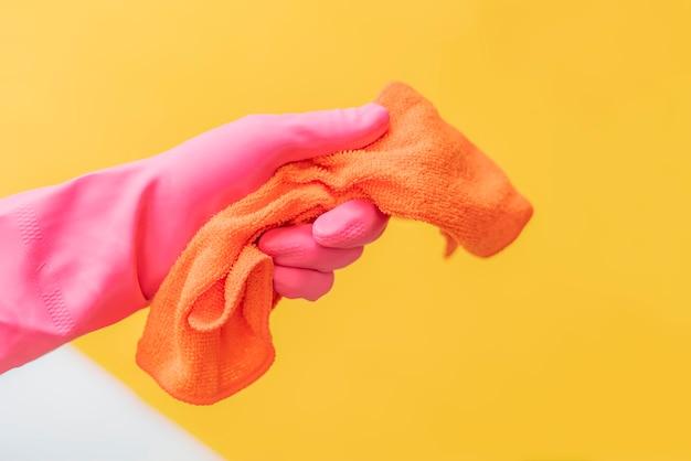 Vrouw hand in roze handschoenen houden doek tegen de effen kleur achtergrond.