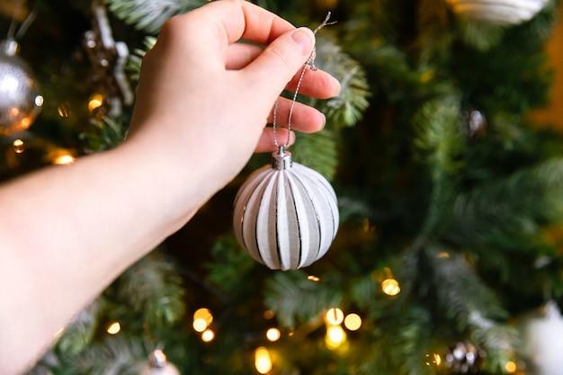 Vrouw hand kerstboom versieren. kerstboom met witte en zilveren versieringen, ornamenten speelgoed en bal. interieur in moderne klassieke stijl. kerstavond thuis, tijd voor feest.