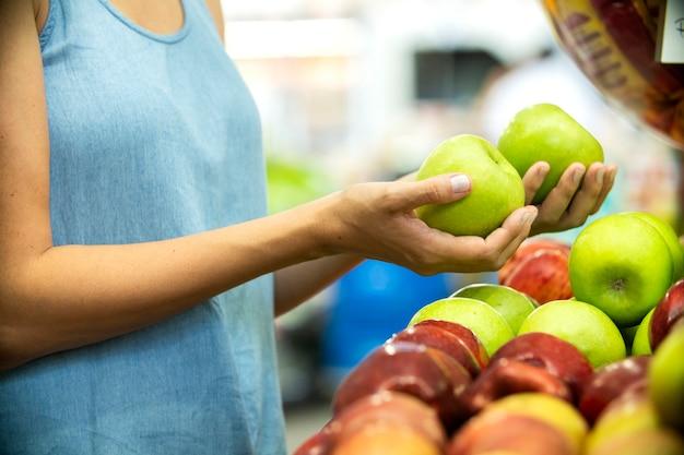 Vrouw hand kiezen groene appel in supermarkt.