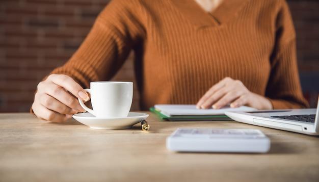 Vrouw hand koffie en kladblok in kantoor