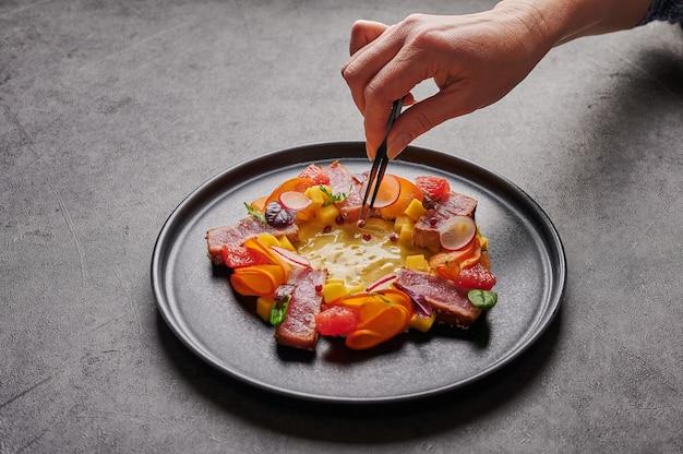 Vrouw hand legt het graan van rode peper met een pincet voor zelfgemaakte salade met tonijnsteak, mangosaus, kruiden en specerijen op een donkere plaat, close-up, voedsel versieren concept