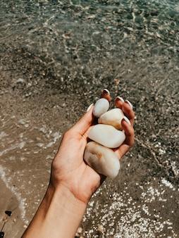 Vrouw hand manicure bedrijf witte mooie stenen boven zee zandstrand zomer strand. natuurlijke achtergrond