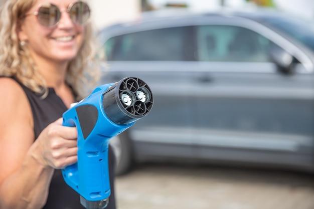 Vrouw hand met auto opladen kabel.