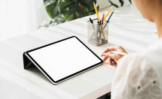 Vrouw hand met behulp van digitale tablet op tafel en het scherm is leeg.