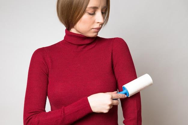 Vrouw hand met behulp van een kleverige roller om rode wollen coltrui van stof te reinigen