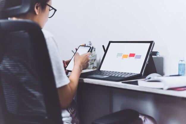 Vrouw hand met behulp van slimme telefoon en laptop op kantoor aan huis.