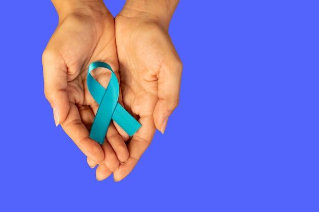 Vrouw hand met blauw lint, prostaatkanker voorlichtingscampagne. vrouw bezorgd over de gezondheid van de man. blauw november.