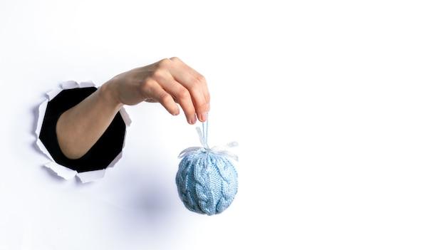 Vrouw hand met blauwe gezellige decoratieve gebreide kerstbal door rond gescheurd gat in wit papier.