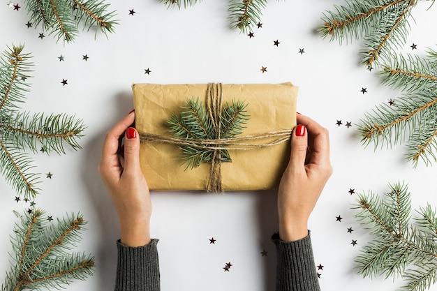 Vrouw hand met cadeau doos kerstdecoratie samenstelling nette fir brunch