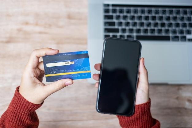 Vrouw hand met creditcard met het gebruik van smartphone en laptop voor online winkelen