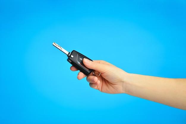 Vrouw hand met een autosleutel afstandsbediening op een blauwe hemelse geïsoleerde achtergrond