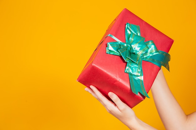 Vrouw hand met een geschenk op gele achtergrond met vrije ruimte voor tekst.
