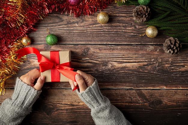 Vrouw hand met een geschenkdoos met rood lint op houten vloer