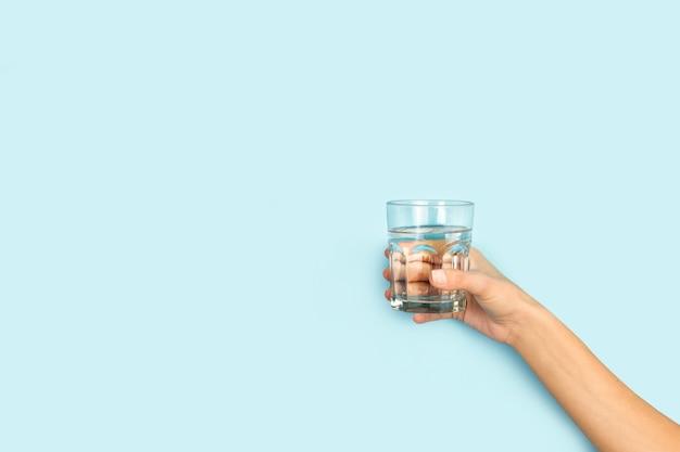 Vrouw hand met een glas water op een lichtblauwe achtergrond